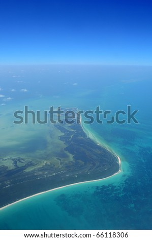 Aerial of the Caribbean coastline near Cancun, Mexico, with coral reefs visible below the sea surface
