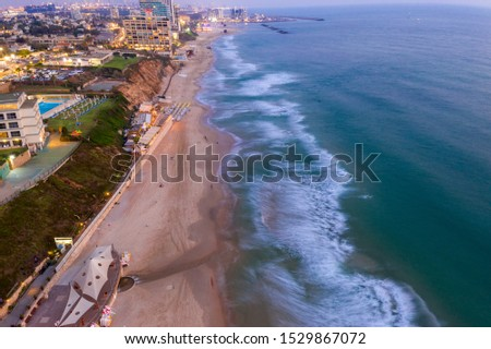Aerial of the coastline near Tel Aviv in Israel with waves and hotels at dusk