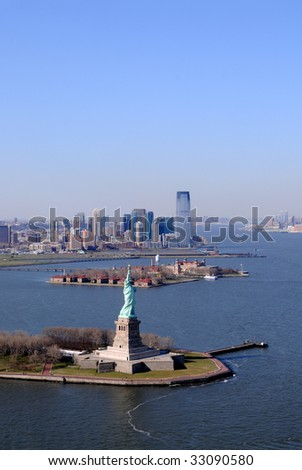 Aerial of the Statue of Liberty in the New York City harbor on a clear spring day. Behind Liberty Island is Ellis Island and then skyscrapers of Jersey City.