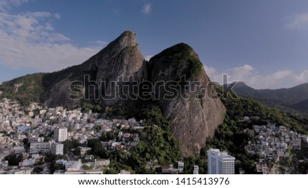 Aerial of Two Brothers mountain tops in Rio de Janeiro with the shantytown of Vidigal on its steep ascent. Skyline landscape of nature and dense urban shantytown community on the slopes. #1415413976