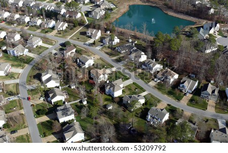 Aerial of uniformly white suburban houses in eastern United States.