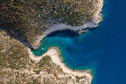 Aerial overhead drone shot of yacht on Adriatic sea curvy cove on Vis Island in Croatia summer morning