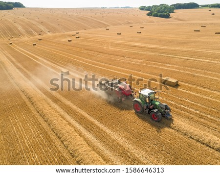 Aerial overhead of tractor baler straw bales in field after wheat harvest in summer on farm