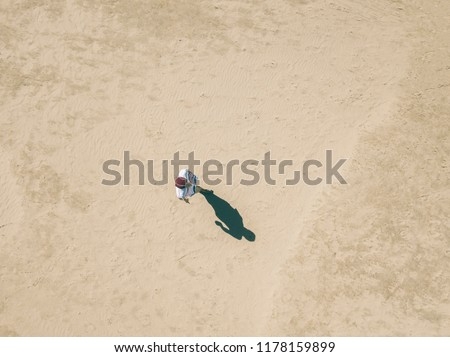 aerial overhead view of young man walking alone in the sandy sea beach, abstract concept background #1178159899