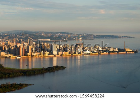 Aerial overview of Porto Alegre, Brazil. Beautiful sunset light illuminating the downtown skyline with reflection on Guaiba River water. Administrative building and football stadium visible. Foto stock ©