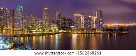 Aerial pano at night of  Miami skyscrapers with colorful lights #1562368261