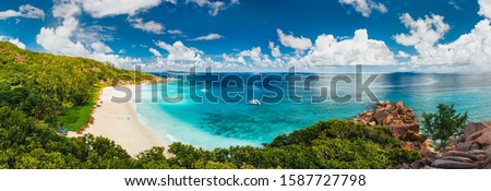 Aerial Pano of Grand Anse beach at La Digue island in Seychelles. White sandy beach with blue ocean lagoon and catamaran yacht moored Photo stock ©
