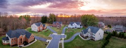 Aerial panorama of brick facade luxury mansion type single family homes neighborhood cul-de-sac street American real estate new construction in Maryland USA with dramatic colorful sunset sky