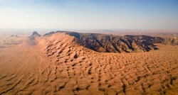 Aerial panorama of Fossil Rock in the Sharjah desert of the United Arab Emirates. Sand meeting the rocky mountain in the UAE desert