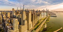 Aerial panorama of New York City waterfront skyline at sunset viewed from above River Side Park, along Joe DiMaggio highway and Riverside Blvd, next to Hudson River.