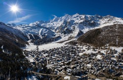 Aerial panorama of the famous Saas Fee village and ski resort by the Dom mountain, the tallest entirely in Switzerland in the alps on a sunny winter day