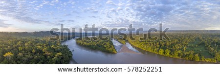 Aerial panorama of the Rio Napo at dawn in the Ecuadorian Amazon with the first rays of the sun illuminating the forest canopy.