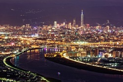 Aerial panorama over Taipei, capital City of Taiwan, on a blue gloomy evening with view of Tamsui & Keelung River, Taipei 101 Tower among high rise buildings & bright city lights in Downtown at dusk