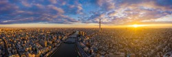 Aerial panorama view by drone of Tokyo Cityscape with Tokyo Sky Tree visible in Tokyo city, Japan on sunrise. Panoramic Dawn view of Tokyo city. Senso-Ji Temple with Sumida river in Japan.