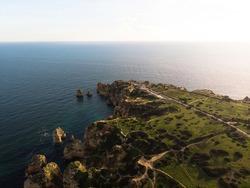 Aerial panorama view of Ponta da Piedade beach cape ocean sea stack rock formations in Lagos Algarve, Portugal Europe