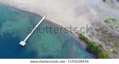 Aerial panorama view of sandy beach with long wooden pier.