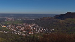 Aerial panorama view over small village Owen located on the foothills of low mountain range Swabian Alb, Germany with historic castle Teck on the mountain in the morning sun in late autumn.