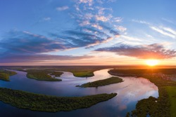 Aerial panoramic landscape with sunset over the river with islands and beautiful clouds on the sky.