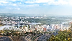 Aerial panoramic overview city centre of Krasnoyarsk skyline with modern residential tower building park trees Yenisei river outside slope rural scenery dramatic clouds cityline urban background view