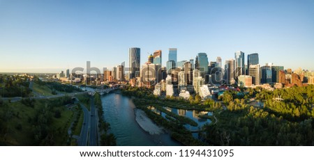 Aerial panoramic view of a beautiful modern cityscape during a vibrant sunny sunrise. Taken in Calgary Downtown, Alberta, Canada. #1194431095