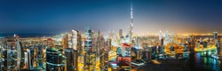 Aerial panoramic view of a big futuristic city by night. Business bay, Dubai, United Arab Emirates. Nighttime skyline.