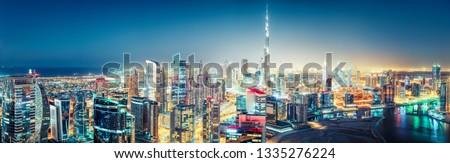 Aerial panoramic view of a big futuristic city by night. Business bay, Dubai, United Arab Emirates. Nighttime skyline.  #1335276224