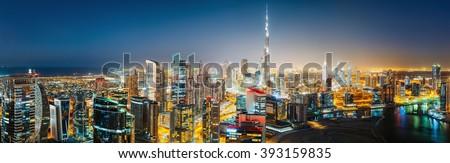 Aerial panoramic view of a big futuristic city by night. Business bay, Dubai, United Arab Emirates. Nighttime skyline.  #393159835