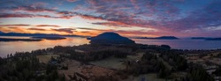 Aerial Panoramic View of a Dramatic Lummi Island Sunrise. Drone shot of Hales Pass, Bellingham Bay and the south end of Lummi island during a beautiful sunrise in the Pacific Northwest.