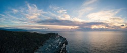 Aerial panoramic view of a rocky shore on the Atlantic Ocean Coast during a vibrant sunny sunset. Taken in Cow Head, Newfoundland, Canada.