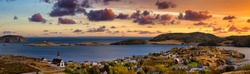 Aerial panoramic view of a small town on the Atlantic Ocean Coast. Dramatic Colorful Twilight Sky. Sunset or Sunrise. Taken in Trinity, Newfoundland and Labrador, Canada.