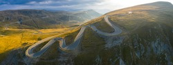 Aerial panoramic view of amazing curved road through the mountains - Transalpina in Romania during an autumn sunrise