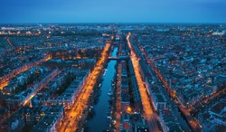 Aerial panoramic view of Amsterdam city in evening. Famous Dutch channels and dancing houses from above. Netherlands, Europe