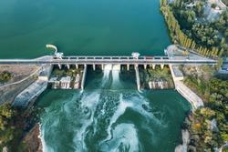 Aerial panoramic view of concrete Dam at reservoir with flowing water, hydroelectricity power station, drone shot.