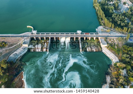 Aerial panoramic view of concrete Dam at reservoir with flowing water, hydroelectricity power station, drone shot. Сток-фото ©