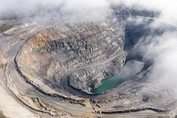 Aerial panoramic view of deep opencast mining quarry. Mining industry and ore extraction