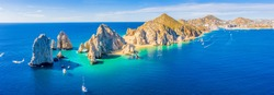 Aerial panoramic view of Lands End and El Arco at the tip of Baja California Sur, with the Cabo San Lucas, Mexico marina in the background