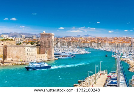 Aerial panoramic view of Marseille Old Port with yachts and boats and the city, mountains in the background. Marseille, Provence, France. Holidays in France