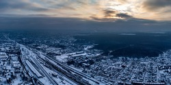 Aerial panoramic view of railway Train depot Kharkov-Sorting station covered in snow with urban view and scenic cold cloudy sky in winter. Kharkiv, Ukraine