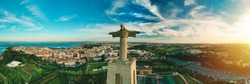 Aerial panoramic view of Sanctuary of Christ the King or Santuario de Cristo Rei at sunset. Christ Statue in Lisbon, Portugal.