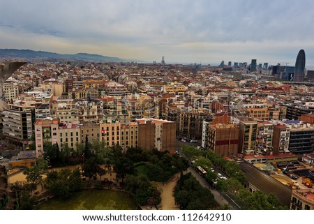 Aerial panoramic view of the crowded, tall buildings city of Barcelona contrasted with open, green space park below from Sagrada familia