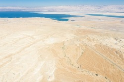 Aerial panoramic view of the Dead Sea and the ancient fortification Masada in the Southern District of Israel situated on top of an isolated rock plateau, eastern edge of the Judaean Desert, Israel