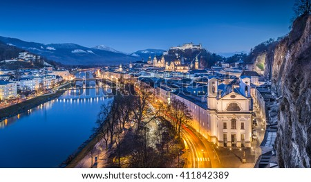 Aerial panoramic view of the famous historic city of Salzburg with Hohensalzburg Fortress and Salzach river in twilight during blue hour at dusk, Salzburger Land, Austria