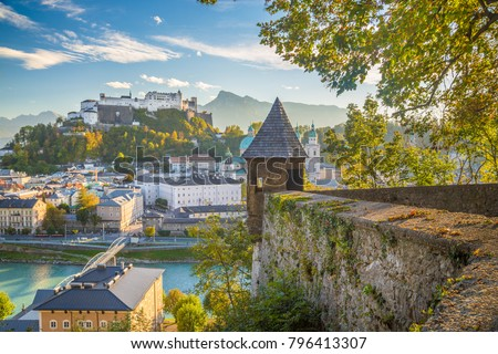 Aerial panoramic view of the historic city of Salzburg with famous Hohensalzburg Fortress and fortification tower in beautiful golden evening light at sunset in fall, Salzburger Land, Austria