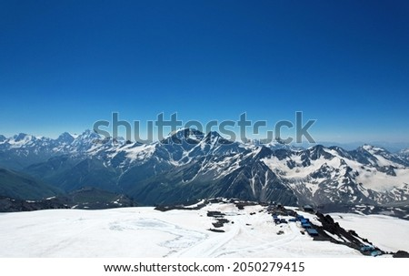 Aerial panoramic view of the Main Caucasus Mountain Ridge from Mount Elbrus, the highest summit in Europe, glacier Seven, incredible blue sky background,  impressive nature landscape in North Caucasus