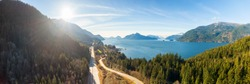 Aerial panoramic view of the Sea to Sky Highway in Howe Sound, North of Vancouver, British Columbia, Canada. Taken during a sunny winter day.