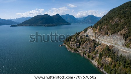 Aerial panoramic view of the Sea to Sky Highway in Howe Sound, North of Vancouver, British Columbia, Canada. Taken during a sunny summer day.  #709670602
