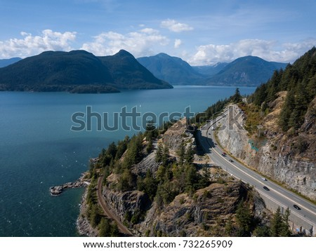 Aerial panoramic view of the Sea to Sky Highway in Howe Sound, North of Vancouver, British Columbia, Canada. Taken during a sunny summer day. #732265909