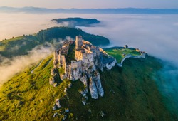 Aerial panoramic view of the Spiš Castle, Slovakia, in the morning sunlight with foggy background
