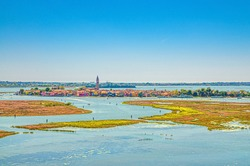 Aerial panoramic view of Venetian Lagoon with Burano island, water canals and swamp. View from bell tower of Torcello island. Veneto Region, Northern Italy. Blue cloudy sky background.