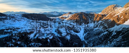 Aerial, panoramic view on winter Passo Rolle from the side of Cima di Vezzana, the highest peak in the Pala group, mountain range of the Dolomites. Sunset in ski area San Martino di Castrozza, Italy.